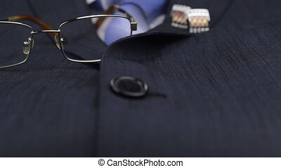 Dolly shot, focus on glasses, tie, cufflinks lies on the suit.