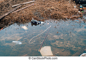 Polluted Beach. Sneakers swim in the river. Rubbish on the river