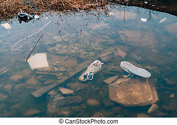 Polluted Beach. Sneakers swim in the river. Rubbish on the...