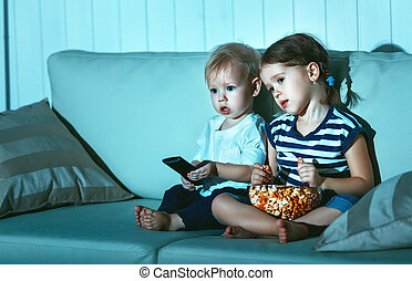 Children brother and sister watching TV in evening -...