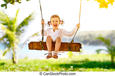 Happy child girl swinging on swing at beach  in summer