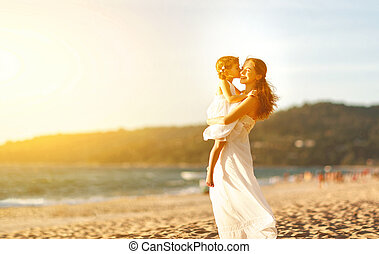 happy family at beach. mother hugging baby daughter at sunset