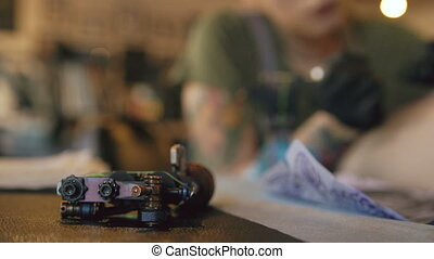 Tattoo machine lying on table with backgroung of yong tattooer woman works drawing on client's leg in studio