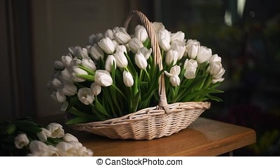 White tulips in a basket. In the background, average plan....