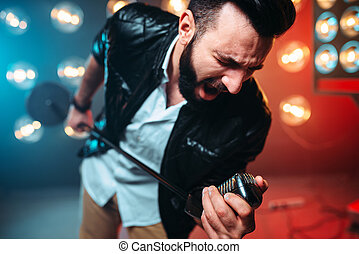 Bearded performer with microphone sing a song - Brutal...