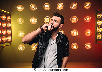 Brutal bearded singer with microphone on the stage with the...