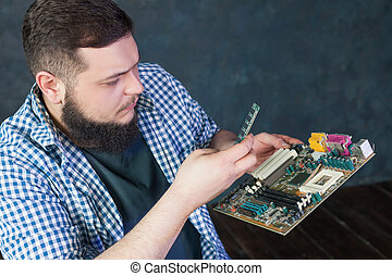 Service engineer fixing problem with pc hardware. Computer...