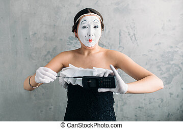 Mime female artist performing with mobile phone. Woman...