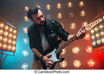 Male solo musican with electro guitar on the stage with the...