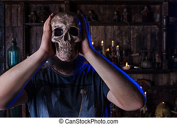 Male person with skull mask on face. Man with horror death...