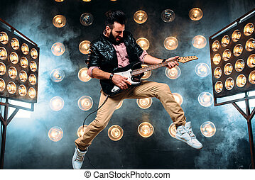 Male pop star with electro guitar on the stage with the...