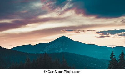 Dramatic mountain forest sunset. Colorful cloudy sky motion....