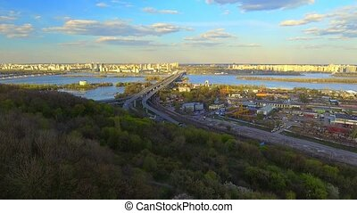 Cityscape. 4k Aerial Shooting with Aircraft Quadrocopter. Camera Fly Over the Kiev City. Roofs of Houses, Streets, Dnipro river, Bridges.