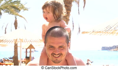 Happy father with cute daughter on his neck in slow motion