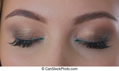 Close up shot of woman opening her eyes. Makeup and beauty...