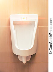Urinal Tile Wall - White urinal for men on tile wall in...