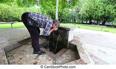 Man drinking from natural spring