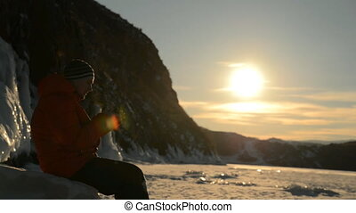 The guy smokes vape at sunset in the winter. - The guy...