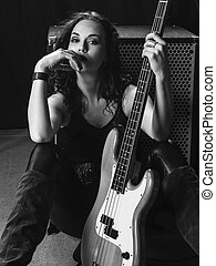 Beautiful bass player sitting with her guitar