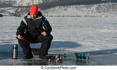 Fisherman is a man in winter fishing. - Fisherman's guy on...