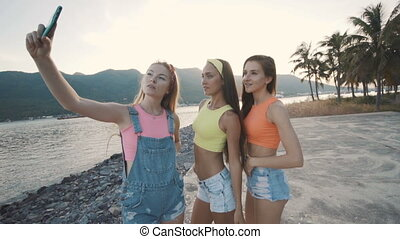 Three friends woman smiling and taking selfie with a smart phone on the beach.