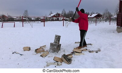 Teenboy chopping the wood at the village yard at winter