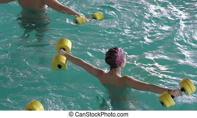 The girl is engaged in aerobics at swimming pol
