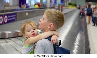 Children stand in the baggage claim area at the airport -...
