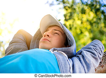 Teenager on the Tree - Happy Teenager resting on the Tree in...