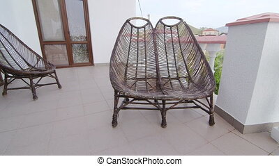 Wicker chairs on balcony at summer day. Two storey home...