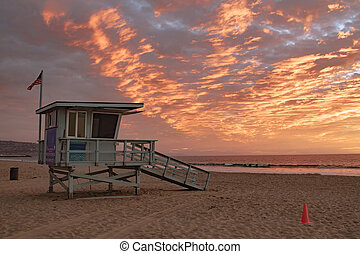 Lifeguard station with american flag on Hermosa beach at sunset