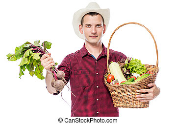 Young man with a basket of vegetables from the garden on a white background