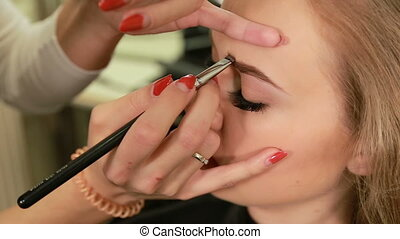 Make-p artist doing makeup of a beautiful young model blonde girl, sharping eyebrows with a brush