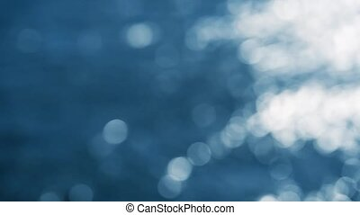 Abstract defocused water flow with reflection of sunlight