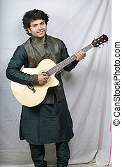 indian male model in green kurta holding guitar smiling