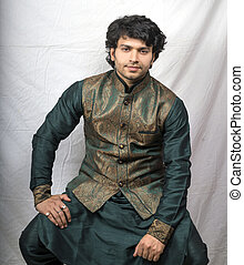indian male model in traditional green kurta sitting pose