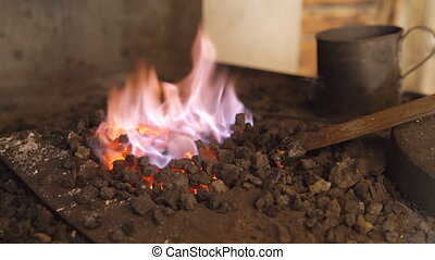Closeup of smithy forge with fire for heating metal at blacksmith workshop