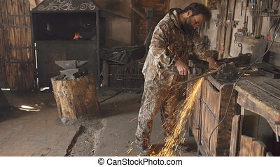 Bearded young man using angle grinder to work on piece of metal in smithy workshop, grinding sparks flying around