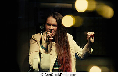 Singer on stage. Concert of a music group in a club in...