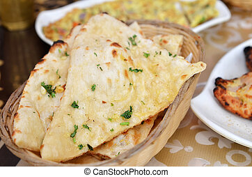 Garlic and coriander naan on a basket. Indian food.