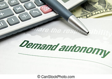 Demand autonomy printed on book with calculator and pen