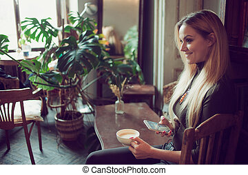 Young female freelancer chatting on mobile phone while...