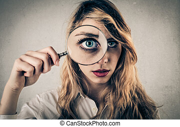 Woman with big eyes - Blonde woman holding magnifying glass...
