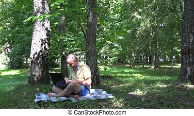 Freelancer self employed man using laptop in nature. -...