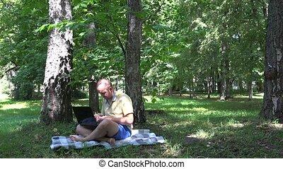 Freelancer self employed man using laptop in nature. -...