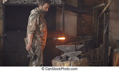 Bearded young man blacksmith manually forging hot metal on...