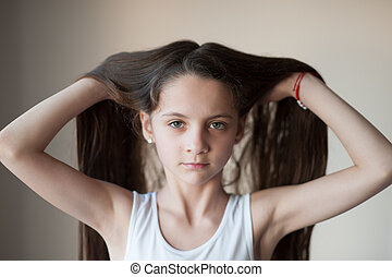 beautiful little girl lifting up her hair by hands -...