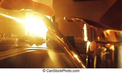Man washing his hands against shining sun, warm colors,...