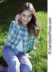 Smiling girl talking on cell phone sitting on grass