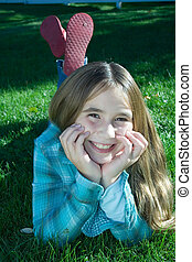 Smiling girl laying in grass - Smiling young girl laying in...
